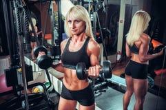 Mujer de la aptitud que hace ejercicios con pesa de gimnasia en el gimnasio Foto de archivo