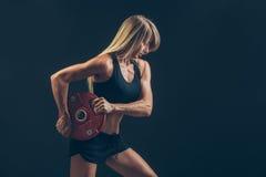 Mujer de la aptitud que hace el entrenamiento del peso levantando pesos pesados Imagen de archivo libre de regalías
