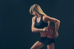 Mujer de la aptitud que hace el entrenamiento del peso por a de elevación Imagen de archivo libre de regalías