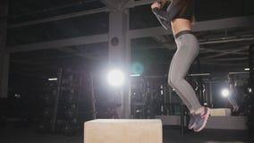 Mujer de la aptitud que hace entrenamiento del salto de la caja en el gimnasio metrajes