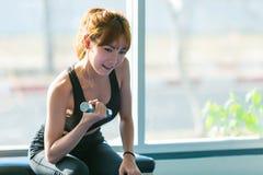 Mujer de la aptitud que hace entrenamientos del bíceps con pesas de gimnasia en un gimnasio imágenes de archivo libres de regalías