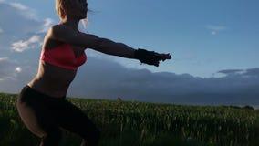 Mujer de la aptitud que hace posición en cuclillas almacen de metraje de vídeo