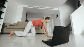 Mujer de la aptitud que mira en el ordenador portátil y que hace ejercicio del gimnasio en el entrenamiento casero metrajes