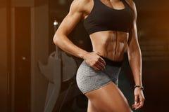 Mujer de la aptitud que muestra el ABS y el vientre plano en gimnasio Muchacha atlética, cintura abdominal, delgada formada Imagen de archivo