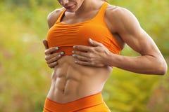 Mujer de la aptitud que muestra el ABS y el vientre plano Muchacha atlética al aire libre, cintura abdominal, delgada formada Imagen de archivo