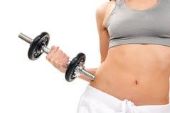 Mujer de la aptitud que resuelve pesas de gimnasia en gimnasia Imagen de archivo libre de regalías