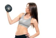Mujer de la aptitud que resuelve pesas de gimnasia en gimnasia Fotos de archivo