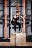 Mujer de la aptitud que salta en el entrenamiento en el gimnasio, ejercicio apto de la caja de la cruz fotos de archivo