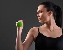 Mujer de la aptitud que se resuelve con pesa de gimnasia verde Fotos de archivo libres de regalías