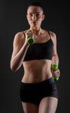 Mujer de la aptitud que se resuelve con pesa de gimnasia verde Imágenes de archivo libres de regalías