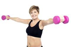 Mujer de la aptitud que se resuelve con pesas de gimnasia rosadas Fotos de archivo libres de regalías