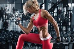 Mujer de la aptitud que se resuelve en el gimnasio, haciendo el ejercicio para el bíceps Muchacha atlética muscular fotos de archivo libres de regalías