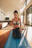 Mujer de la aptitud que se sienta en la estera de la yoga y que usa el teléfono móvil Imagen de archivo libre de regalías