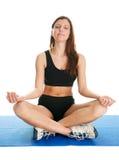 Mujer de la aptitud que se sienta en la posición de la yoga del loto Fotos de archivo libres de regalías