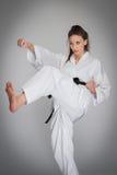 Mujer de la autodefensa del sacador del retroceso en el entrenamiento del karate Foto de archivo