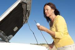 Mujer de la avería del coche que controla el petróleo Fotografía de archivo