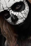 Mujer de la belleza con el cráneo asustadizo en su cara Foto de archivo