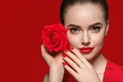 Mujer de la belleza con el pelo rizado hermoso y los labios de la flor color de rosa foto de archivo