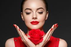Mujer de la belleza con el pelo rizado hermoso y los labios de la flor color de rosa imagen de archivo libre de regalías