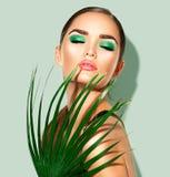 Mujer de la belleza con la hoja de palma verde natural Retrato de la muchacha modelo con maquillaje perfecto, sombreadores de ojo imágenes de archivo libres de regalías