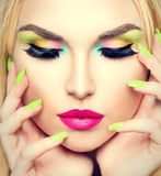 Mujer de la belleza con maquillaje vivo y esmalte de uñas colorido Fotografía de archivo