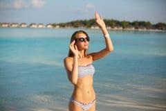 Mujer de la belleza de la playa de la salud del balneario en el traje de baño del bikini que se relaja y baño de sol cerca de lag Imagen de archivo