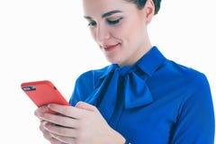Mujer de la belleza en blusa azul usando y leyendo un teléfono elegante aislado en un fondo blanco Fotografía de archivo libre de regalías