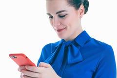 Mujer de la belleza en blusa azul usando y leyendo un teléfono elegante aislado en un fondo blanco Fotos de archivo libres de regalías