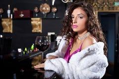 Mujer de la belleza en el soporte blanco del abrigo de pieles en la barra Fotos de archivo libres de regalías