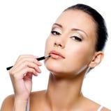 Mujer de la belleza que aplica el lápiz labial Fotografía de archivo