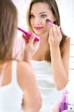 Mujer de la belleza que aplica maquillaje Fotos de archivo