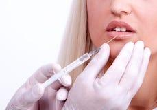 Mujer de la belleza que da inyecciones del botox Foto de archivo libre de regalías