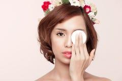 Mujer de la belleza que muestra la esponja de algodón en cara - estafa del cuidado del ojo y de piel Fotografía de archivo libre de regalías