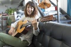 Mujer de la belleza que se sienta en un dofa y que toca la guitarra Fotos de archivo