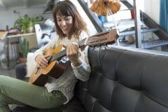 Mujer de la belleza que se sienta en un dofa y que toca la guitarra Imagenes de archivo