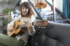 Mujer de la belleza que se sienta en un dofa y que toca la guitarra Imágenes de archivo libres de regalías