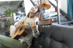 Mujer de la belleza que se sienta en un dofa y que toca la guitarra Imagen de archivo
