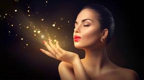 Mujer de la belleza que sopla el polvo mágico con los corazones de oro imágenes de archivo libres de regalías