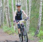 Mujer de la bici de montaña que completa un ciclo cuesta abajo en el bosque del abedul Fotografía de archivo