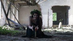 Mujer de la bruja en ropa gótica que maldice durante ritual usando una vela en un edificio arruinado destruido metrajes