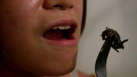 Mujer de la cámara lenta que come la araña para la cena en restaurante asiático en Camboya metrajes