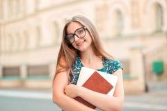 Mujer de la chica joven del estudiante que sostiene el ordenador port?til de los libros que sonr?e afuera imagen de archivo libre de regalías