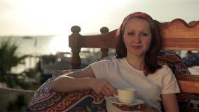 Mujer de la chica joven que se relaja en mirador de la calle del café almacen de video