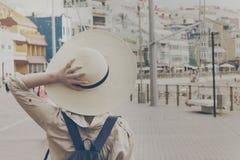 Mujer de la chica joven que sostiene sombrero de paja que camina en la calle ur Foto de archivo