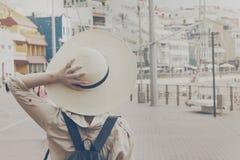 Mujer de la chica joven que sostiene sombrero de paja que camina en la calle ur Fotografía de archivo libre de regalías