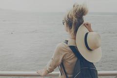 Mujer de la chica joven que sostiene sombrero de paja que mira en el océano Tr Imagen de archivo libre de regalías