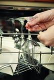 Mujer de la cocina con una copa de vino limpia Fotos de archivo