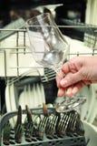 Mujer de la cocina con una copa de vino limpia Imágenes de archivo libres de regalías