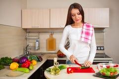 Mujer de la cocina que hace la ensalada Foto de archivo
