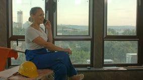Mujer de la construcción que hace llamada mientras que teniendo una rotura metrajes